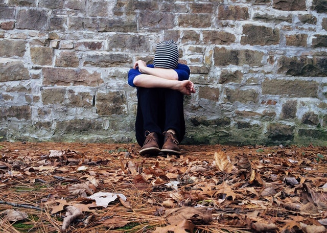 this is a picture of a distressed person burying their face and head against their knees. They are sitting alone against a brick wall. They look like they have had enough. Have you had enough? Do you need my help? Are you looking for counselling in Crawley to help with or manage your mild depression?